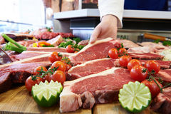 Butcher Showing Customer Sirloin Steak In Refrigerated Display Royalty Free Stock Images