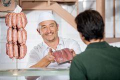 Butcher Showing Packed Sausages To Customer Royalty Free Stock Image