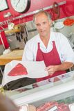Butcher showing steak to customer. Appraise royalty free stock photos