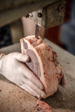 Butcher is slicing beef meat. On bandsaw at store Royalty Free Stock Photos