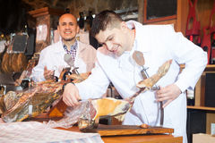 Butcher slicing jamon and smiling Stock Images