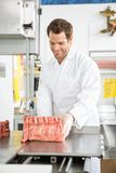 Butcher Slicing Meat On Bandsaw In Shop Royalty Free Stock Photography