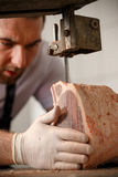 Butcher is slicing meat Royalty Free Stock Photos