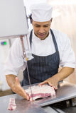 Butcher slicing meat Royalty Free Stock Images