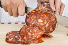 Butcher slicing a Spanish sausage called morcon Stock Photo