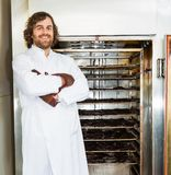 Butcher Standing Arms Crossed In Front of Smoker. Portrait of happy male butcher standing arms crossed in front of smoker oven at shop Royalty Free Stock Photo