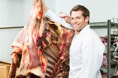 Butcher Standing Beside Beef in Cooler Royalty Free Stock Photography