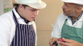 Butcher Teaching Apprentice How To Prepare Meat Royalty Free Stock Photography