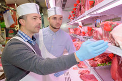 Butcher teaching young one how to sell meat Royalty Free Stock Images