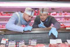 Butcher teaching young one how to sell meat. Butcher teaching a young one how to sell meat Royalty Free Stock Photo