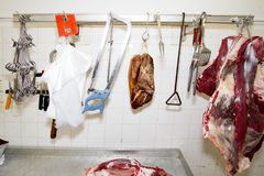 WORK PLACE OF BUTCHER. BEEF AND PORK HANGING ON HOOK. BUTCHER TOOLS, KNIFE, SAW, HATCHET. WORKTABLE BY BUTCHER. BEEF AND PORK SLICE royalty free stock images