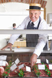Butcher in uniform behind meat counter Stock Photo