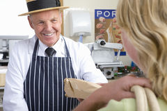 Butcher in uniform selling meat to customer Royalty Free Stock Photos