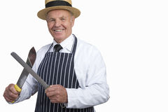 Butcher in uniform sharpening knife, cut out Stock Photos