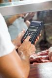 Butcher Using Electronic Card Machine In Shop Royalty Free Stock Photography