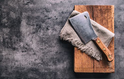 Butcher. Vintage butcher meat cleavers with cloth towel on dark concrete or wooden kitchen  board Royalty Free Stock Photo