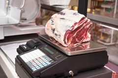 Butcher weighing meat at display cabinet in the butchery Royalty Free Stock Images
