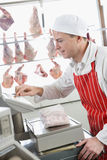 Butcher weighing meat on scale in shop Stock Photography