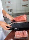 Butcher Weighing Meat On Weight Scale Stock Photo