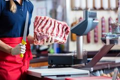 Butcher woman cutting piece of rib meat in her shop Royalty Free Stock Images