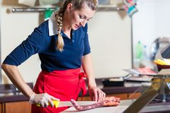 Butcher woman cutting piece of rib meat in her shop royalty free stock photos