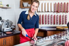 Butcher woman cutting a sausage in the shop royalty free stock images