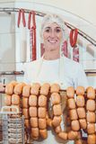 Butcher woman showing sausages on a rail stock photography