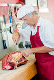 Butcher working on large cut beef. Butcher working on a large cut of beef stock photography