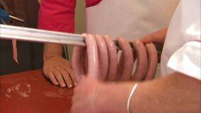 Butcher wrapping sausages in a link around a bar. Close up of a butchers hands wrapping sausages in a link around a bar, to be cooked in an oven or cured stock video