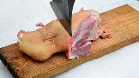 Butcher wrong cuts pork knuckle with an ax stock footage