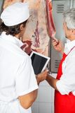 Butchers Analyzing Meat Hanging In Butchery Stock Image