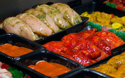 Butchers display counter. Fresh chicken fillets marinaded in chinese coatings on a Butchers display counter for making your own easy stir fries Stock Photos