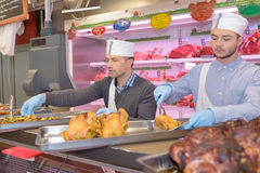 Butchers displaying cooked chicken on top counter. Butchers displaying cooked chicken on top of counter stock image