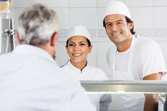 Butchers Looking At Customer In Store Royalty Free Stock Images