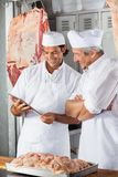 Butchers Looking At Tablet Computer In Butchery Royalty Free Stock Photos