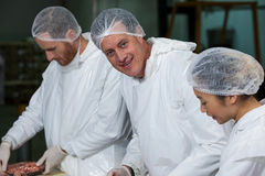 Butchers packing raw sausages. At meat factory Stock Images