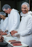 Butchers packing raw sausages. At meat factory Royalty Free Stock Images