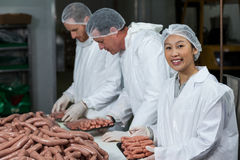 Butchers packing raw sausages. At meat factory Royalty Free Stock Photo
