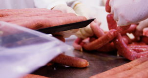 Butchers packing sausages in container stock video footage