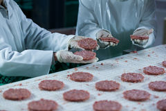 Butchers processing hamburger patty. At meat factory Royalty Free Stock Images