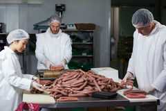 Butchers processing sausages Royalty Free Stock Photo