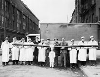 Butchers showing off a long sausage in front of a truck. (All persons depicted are no longer living and no estate exists. Supplier grants that there will be no stock images