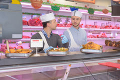 Butchers standing behind counter in supermarket. Butchers standing behind counter in a supermarket Royalty Free Stock Photography