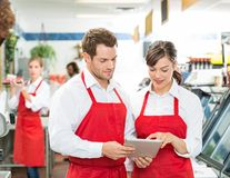 Butchers Using Digital Tablet At Store Stock Images
