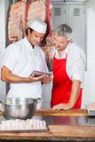 Butchers Using Tablet Computer Together In Stock Photography