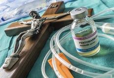 Buteleczka z dawkami pentobarbital obok krucyfiksu, debata między życie i śmierć, przekonanie religijne w obliczu eutanazji zdjęcie royalty free