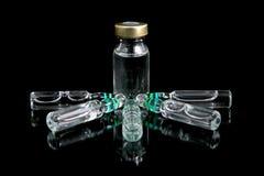 Buteleczki medyczny odosobniony na czarnym tle Serum w ampułce Zdjęcia Stock