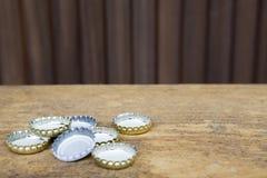 Butelek nakrętki na nieociosanym drewnianym tle Zdjęcie Royalty Free