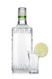 Buteljera av försilvrar tequila och skjutit med limefruktskivan Royaltyfri Foto