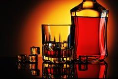 Buteljera av whisky och exponeringsglas med is royaltyfria foton